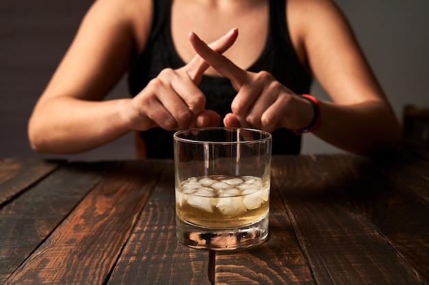 ノーと言って、飲酒を避けている女性。アルコール依存症、中毒、リハビリテーションの概念。