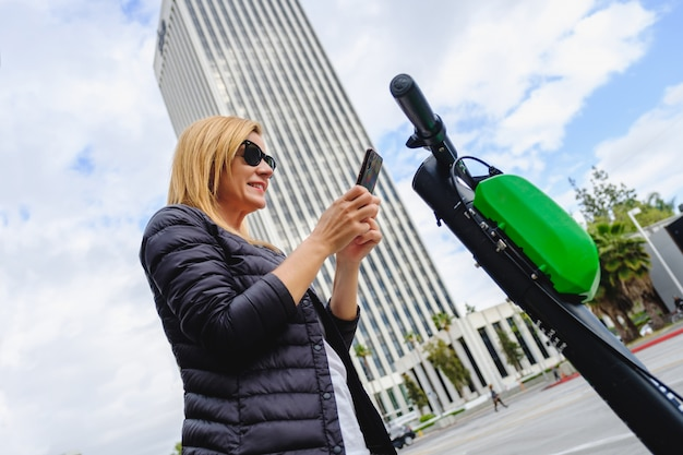 Woman scanning the qr code with her phone to rent an electric scooter