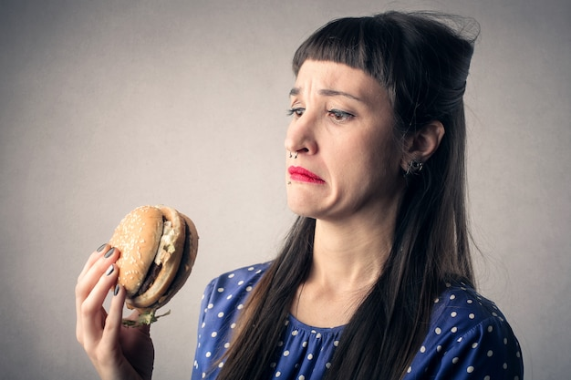 Woman scared with a big hamburger