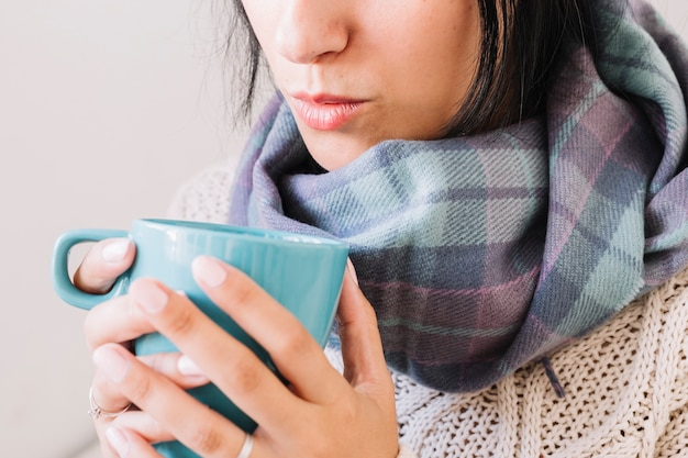 Woman in scarf blowing on cup