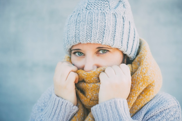 Woman in a scarf and cap is showing she is cold.