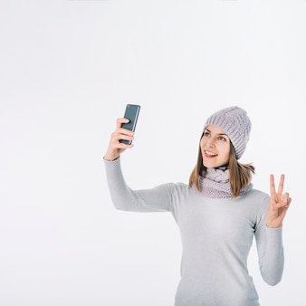 Woman in scarf and hat taking selfie
