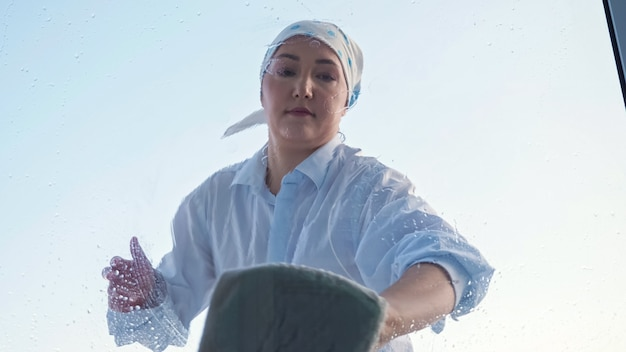 Woman in a scarf and shirt washes the window with a rag.