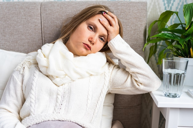 Woman in scarf with red nose feeling headache and fever