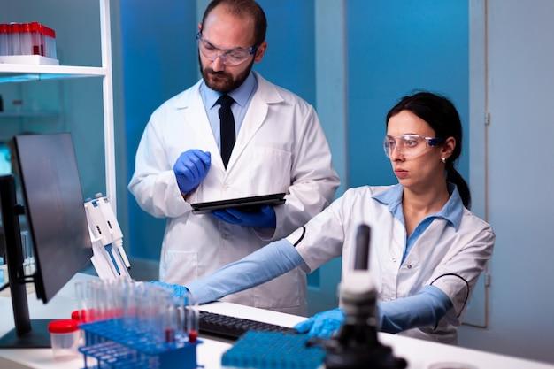 専門の技術機器を使用して医療ラボでウイルスの専門知識を研究している女性科学者と男性医師