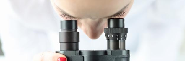 Женщина-ученый-химик, глядя через микроскоп крупным планом, концепция лабораторной диагностики