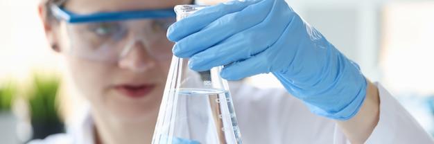 물을 확인 그녀의 손 근접 촬영에 투명 액체와 플라스크를 들고 여자 과학자