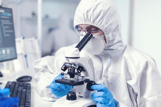 Женщина-ученый в labratoruy ищет лекарство от коронавируса, одетая в костюм ppe. химик-исследователь во время глобальной пандемии с проверкой образца covid-19 в биохимической лаборатории