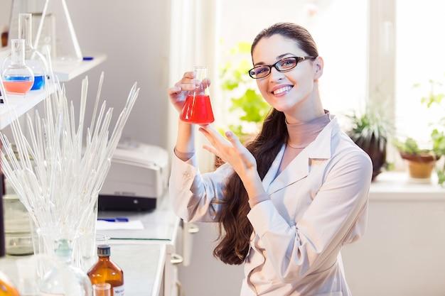 ビーカーのポーズで実験室の女性科学者