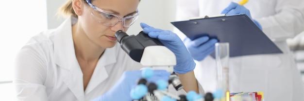 보호 안경을 쓴 여성 과학자는 현미경을 통해 살펴보고 화학 실험실에서 조수를 훈련시킵니다.