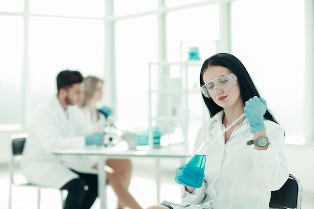 女性科学者が液体のサンプルを採取します