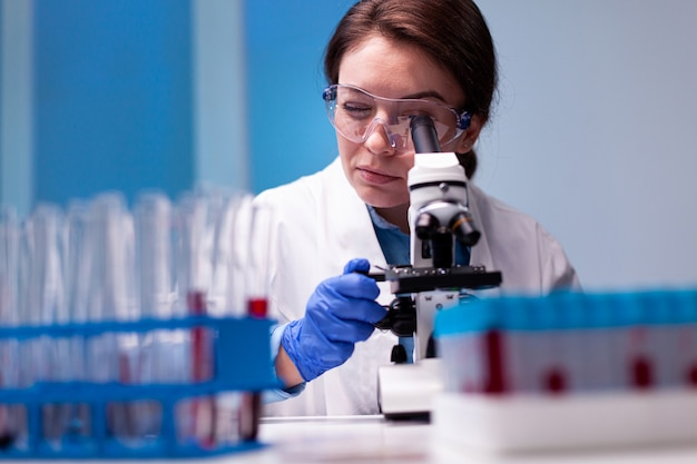Woman scientist in white coat looking in high end microscope for pharmacy expertise