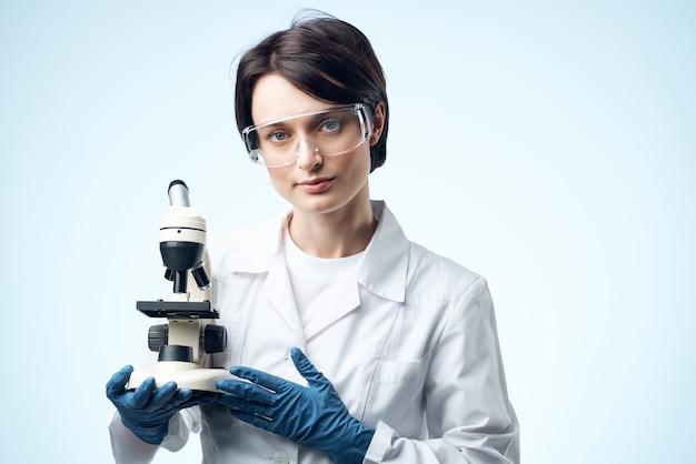 技術研究の手に顕微鏡を持っている女性科学者