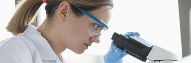 안경을 쓴 여성 과학자는 미지의 미생물을 현미경으로 감지하여 연구를 수행합니다.