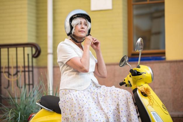 Woman on scooter wearing helmet.