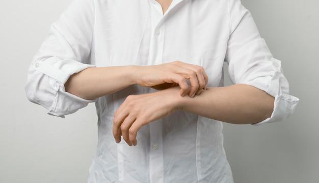 女性は彼女の腕を掻く