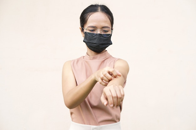 Woman scratching arm from itching on light gray background