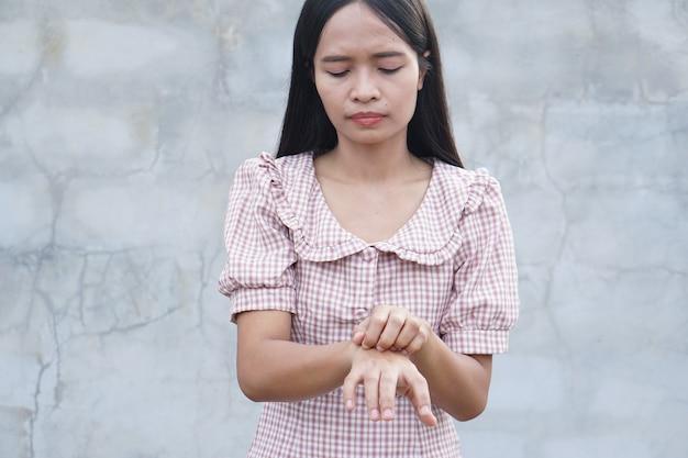Женщина чешет руку от зуда на сером фоне