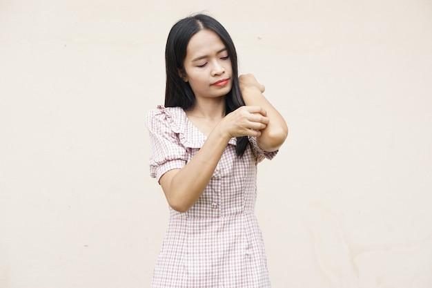 Женщина чешет руку от зуда на светло-сером фоне