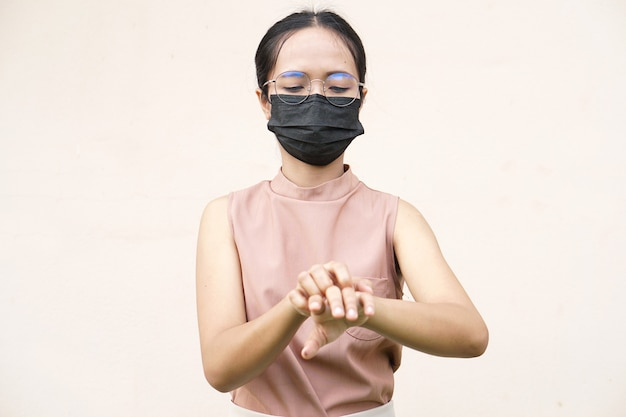 Женщина чешет руку от зуда на светло-сером фоне Premium Фотографии