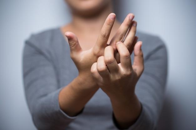 彼女の手を引っ掻く女性