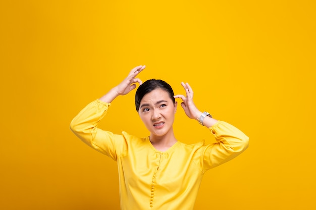 Woman scratching her head isolated over yellow wall