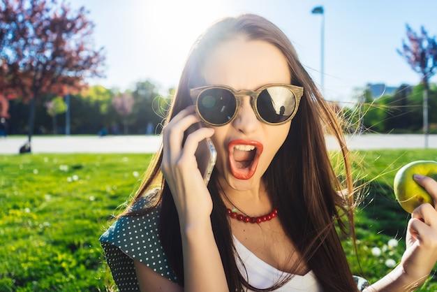 女性は携帯電話に叫び、叫び、携帯電話と議論し、怒っている