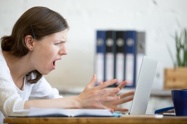 Woman screaming at laptop Premium Photo