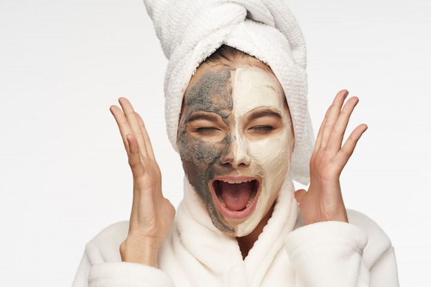 Woman screaming with facial mask, beauty concept