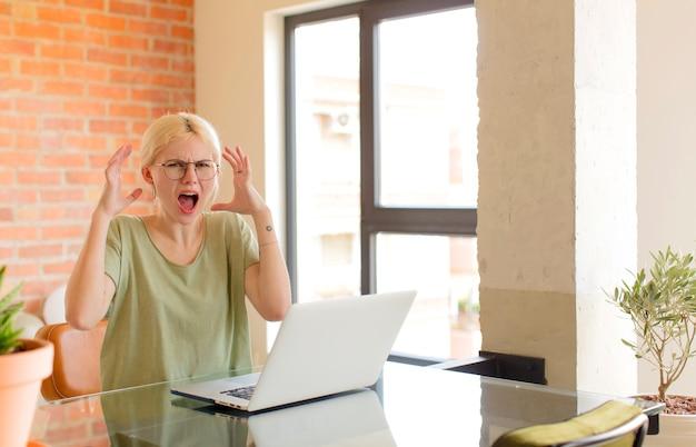 Женщина кричит с поднятыми руками, чувствуя ярость, разочарование, стресс и расстройство