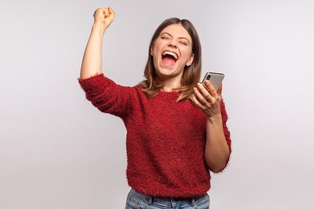 Женщина кричит с мобильным телефоном в руке, празднует победу в онлайн-ставках