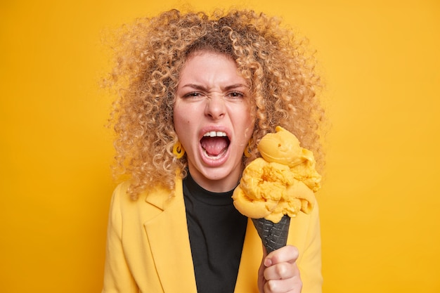 Woman screams angrily keeps mouth opened holds ice cream expresses negative emotions and feelings dressed in stylish jacket has sweet tooth eats junk food high in calories