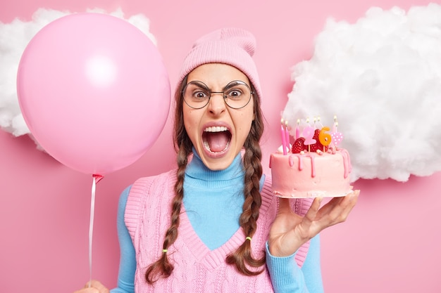 Woman screams loudly keeps mouth widely opened being irritated because of something holds inflated balloon and birthday cake expresses negative emotions. celebration concept