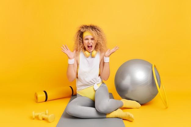 Женщина громко кричит, раздвигая ладони, выражает негативные эмоции, чувствует раздражение после тяжелой фитнес-тренировки с гантелями, хула-хуп и швейцарский мяч