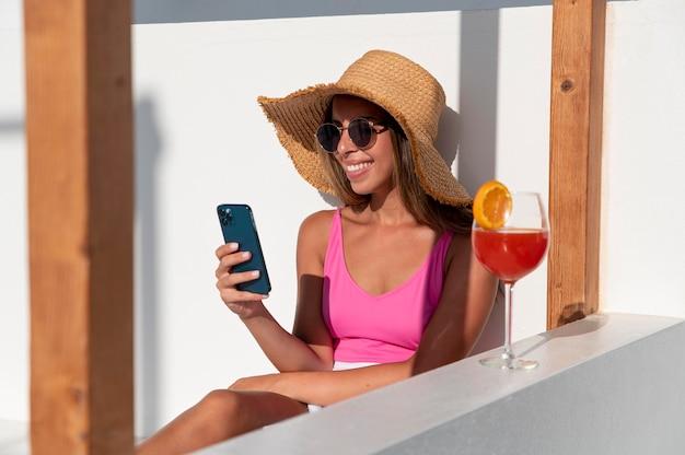 休暇中にスマートフォンでフィードをスクロールする女性
