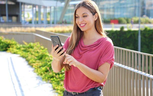 Woman scrolling messages on smartphone app to chat in city street