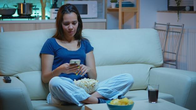 팝콘을 먹고 영화를 보고 있는 전화를 스크롤하는 여자. 외롭고 즐거운 행복한 여성은 스마트폰으로 읽고, 쓰고, 검색하고, 밤에 휴식을 취하는 기술 인터넷을 사용하여 즐겁게 웃고 있습니다.