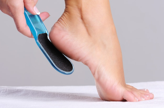Woman scrubbing  heel in beauty salon use the   tool for pedicure