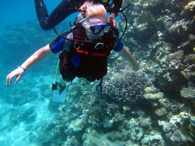 Женщина аквалангист и красивый красочный коралловый риф под водой