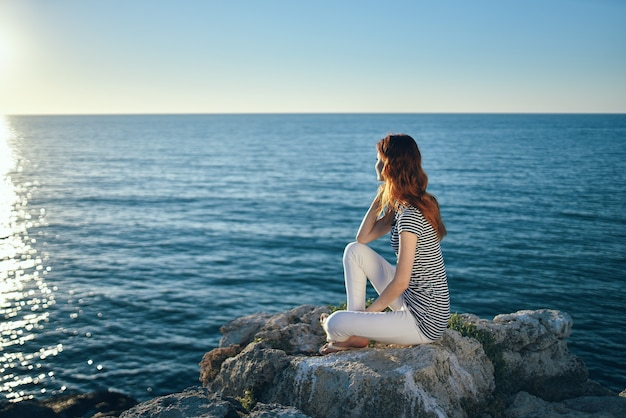 Woman on the sea in the mountains in the evening at sunset high cliffs mountains. high quality photo