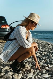 Woman at sea touching rocks
