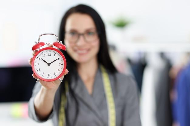赤い目覚まし時計のクローズアップを保持している女性の裁縫師。注文コンセプトの作成条件