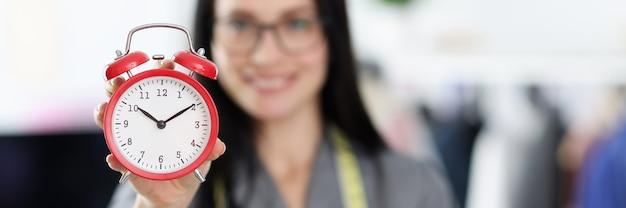 주문 개념을 만드는 빨간색 알람 시계 근접 촬영 조건을 들고 여자 재 봉사