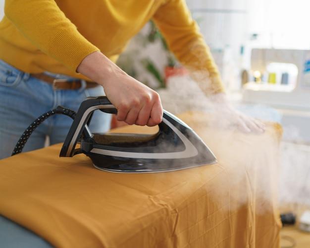 Женщина-швея гладит оранжевую ткань во время работы на своем рабочем месте