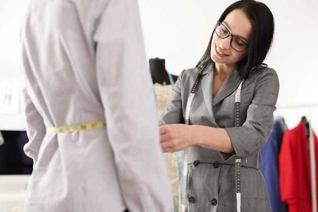 센티미터 테이프 수리 및 옷 수리로 클라이언트 허리를 측정하는 여성 재봉사