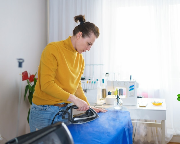 Женщина-швея или домохозяйка гладит ткань перед шитьем во время работы на своем рабочем месте