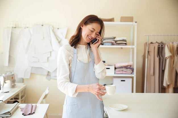 Woman seamstress talking on phone and drinking coffee