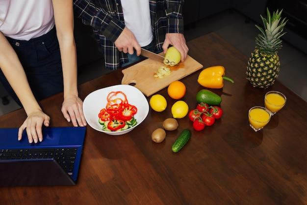 彼女の男性がサラダのためにピーマンを切る間、女性はラップトップで新しいレシピを検索します