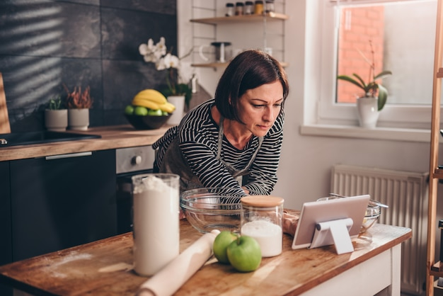 Woman searching apple pie recipe on the tablet