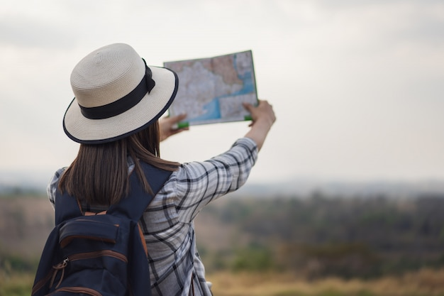 Woman searching direction on location map while traveling